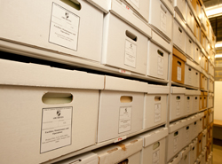 View of university records in archival boxes in the archives storage facility in Aquinas Hall